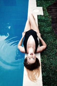 Schönes sexy luxuriöses mädchen liegt am rande des schwimmbades und sonnt sich im schwarzen bikini, der sich auf einer tropischen insel entspannt, eine draufsicht