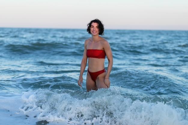Schönes sexy mädchen am meeresstrand in einem roten kleid betrachtet den flatternden wind der kamerahaare bei sonnenuntergang. nahaufnahme eines modischen nackten mädchens in einem badeanzug. nahaufnahmemodeporträt des modells im freien
