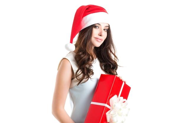 Schönes sexy mädchen, das weihnachtsmannhut mit weihnachtsgeschenk trägt.
