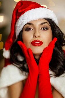 Schönes sexy mädchen, das weihnachtsmannkleidung auf dem hintergrund der weihnachtsbeleuchtung trägt