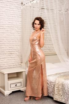 Schönes sexy mädchen in einem langen kleid im hotel