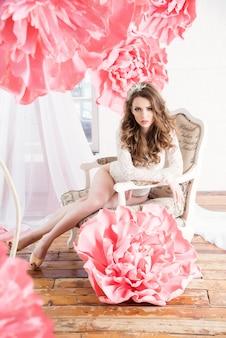 Schönes sexy mädchen in einem langen kleid mit sehr großen rosa blumen, die am fenster sitzen