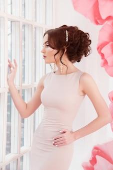 Schönes sexy mädchen in einem langen kleid mit sehr großen rosa blumen.