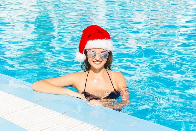Schönes sexy mädchen in santa claus-hut mit gebräunter haut in der schwarzen bikinisonnenbrille. sauberes wasser im kurhotel im urlaub