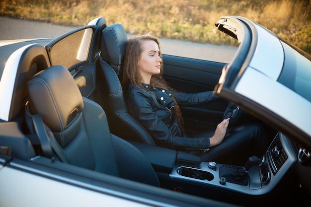 Schönes sexy mädchen mit dem langen haar in einer lederjacke und in lederhosen in der sonnenbrille sitzt in einem teuren auto bei sonnenuntergang.