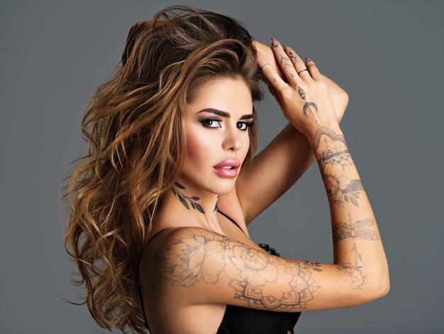 Schönes sexy mädchen mit einem tattoo auf dem körper. porträt der attraktiven frau des jungen erwachsenen mit braunen haaren.