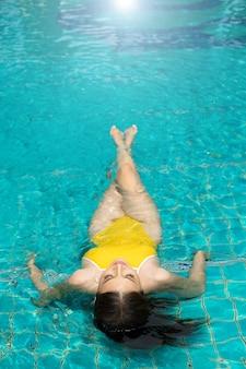 Schönes sexy mädchen mit schlankem körper im gelben badeanzug bikini