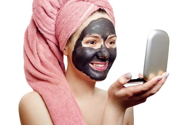 Schönes sexy mädchen mit schwarzer gesichtsmaske auf dem weißen hintergrund, nahaufnahmeporträt, isoliert, rosa handtuch auf ihrem kopf, mädchen schaut mit vergnügen auf sich selbst in einem kleinen spiegel, lächelt