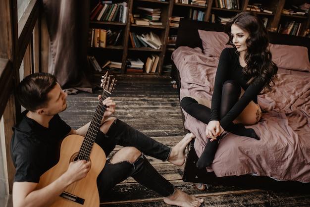 Schönes sexy mädchen und ihr freund, der gitarre spielt