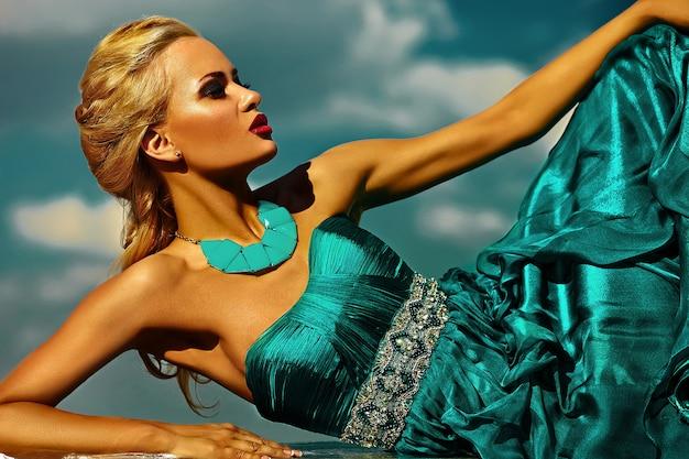 Schönes sexy stilvolles blondes modell der jungen frau des blickes der hohen mode zauber mit den hellen roten lippen des make-up mit perfekter sonnengebadeter haut mit schmuck draußen in der modeart, wenn langes blaues kleid hinten geglättet wird