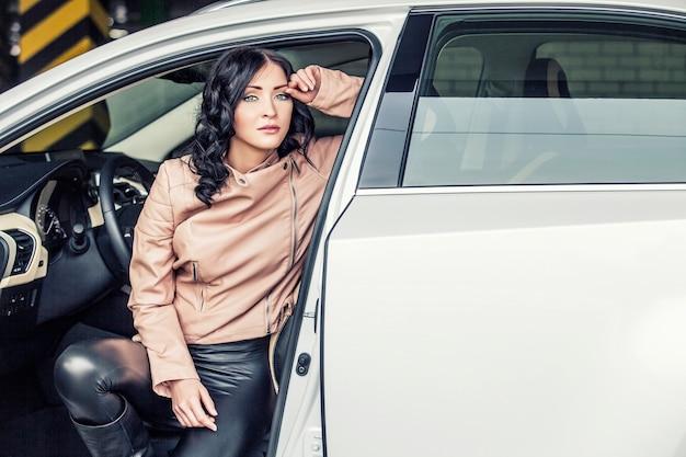 Schönes sexy weibliches modell in der lederkleidung mit einem weißen auto auf dem parkplatz
