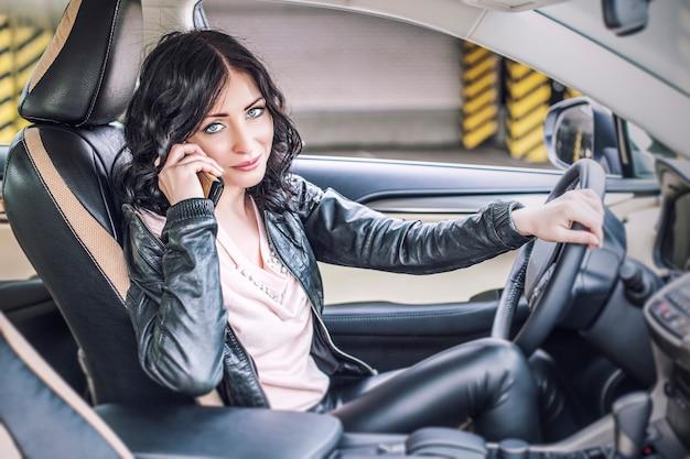 Schönes sexy weibliches modell in lederkleidung mit einem weißen auto und einem smartphone auf dem parkplatz