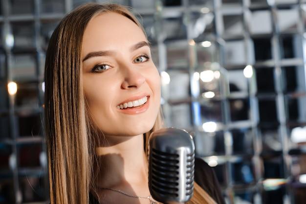 Schönes singendes mädchen. schönheitsfrau mit mikrofon. glamour model sänger. karaoke-lied.