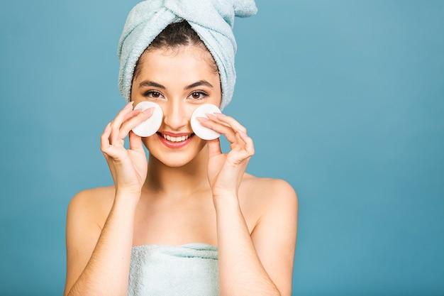 Schönes sinnliches mädchen, das ihr gesicht mit wattestäbchenpad reinigt. foto des mädchens nach dem bad im bademantel und im handtuch auf ihrem kopf lokalisiert auf blauem hintergrund.