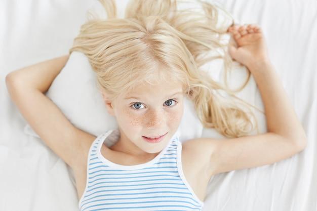 Schönes sommersprossiges mädchen mit blauen augen und hellem haar, gestreiftem t-shirt tragend, auf weißem kissen im schlafzimmer liegend