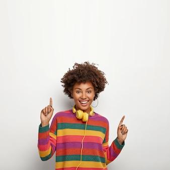 Schönes sorgloses hipster-mädchen mit afro-frisur, bewegt sich gegen weiße wand, zeigt nach oben, sagt ihren text hier, verwendet gelbe kopfhörer zum hören von lieblingsmusik, trägt gestreiften farbigen pullover