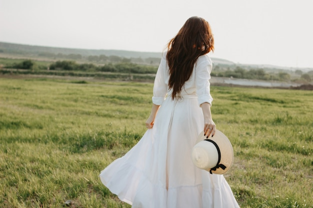 Schönes sorgloses langes haarmädchen in der weißen kleidung und im strohhut genießt das leben auf dem naturgebiet bei sonnenuntergang