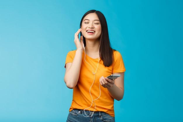 Schönes sorgloses süßes asiatisches mädchen genießen tolle musik, die die stimmung steigert, lieblingslieder zu hören, kopfhörer berühren, augen vor freude schließen, mitsingen, smartphone-ständer auf blauem hintergrund halten Premium Fotos