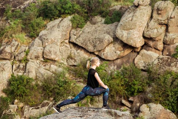 Schönes sportliches blondes frauentraining, das sich auf felsen im canyon ausdehnt