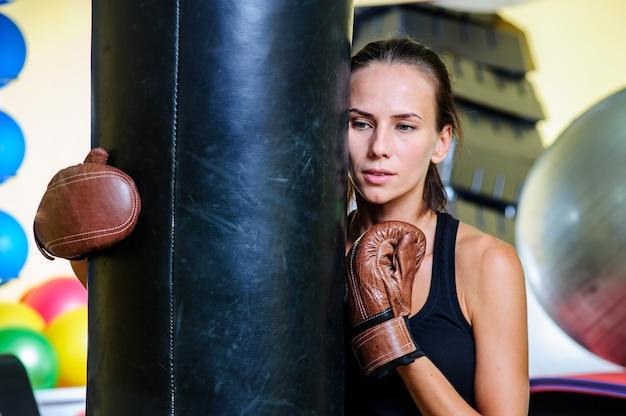 Schönes sportliches frauenboxen mit rotem boxsack im fitnessstudio