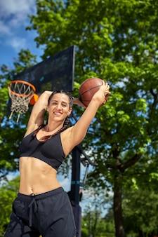 Schönes, sportliches lateinamerikanisches mädchen mit einem basketball unter dem ring auf einer straßenbasketballplatz-sportmotivation, gesunder lebensstil