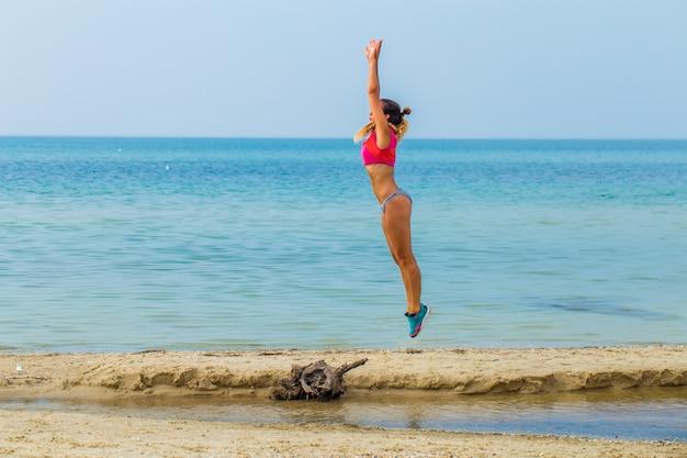 Schönes sportliches mädchen am strand sport