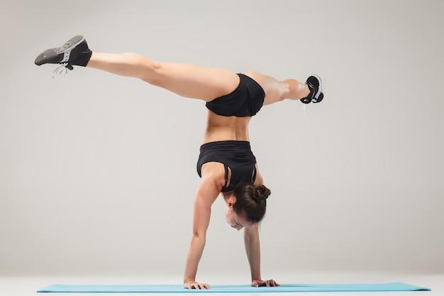 Schönes sportliches mädchen, das in der akrobatenhaltung oder in der yoga-asana auf grauem hintergrund steht