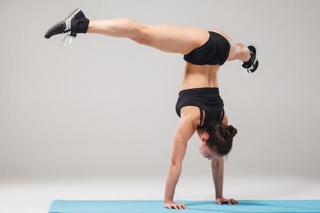 Schönes sportliches mädchen, das in der akrobatenhaltung oder in der yoga asana steht