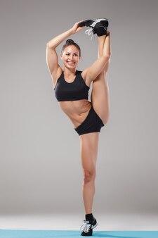Schönes sportliches mädchen, das in der akrobatenhaltung oder in der yoga-asana steht