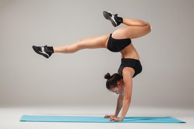 Schönes sportliches mädchen, das in der akrobatenhaltung steht