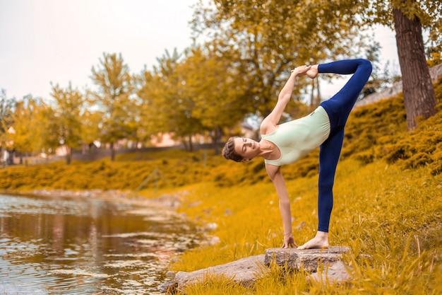 Schönes sportliches mädchen, das in der halbmondhaltung, ardha chandrasana-übung schlank steht. yoga-übungen auf dem grünen rasen im herbst vor dem hintergrund der natur