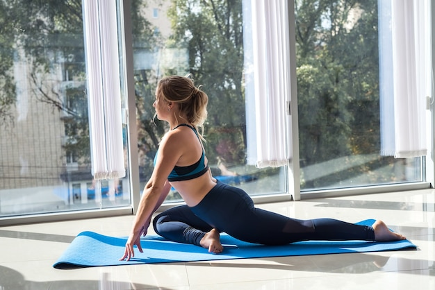 Schönes sportliches mädchen in der sportkleidung, die in der matte sitzt, die zu hause nahe fenster ausarbeitet. gesundheitskonzept