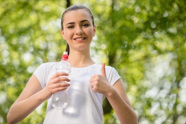 Schönes sportliches mädchen in trinkwasser des weißen t-shirts.