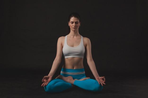 Schönes sportliches yogimädchen übt yoga asana