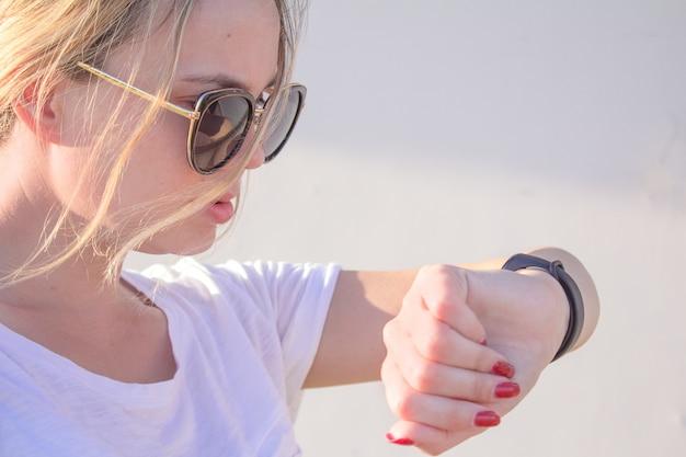 Schönes sportmädchen berührt ihr fitbit armband nach dem training