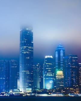 Schönes stadtbild mit beleuchtetem gebäude, das im nebel in hong kong, china eingehüllt wird