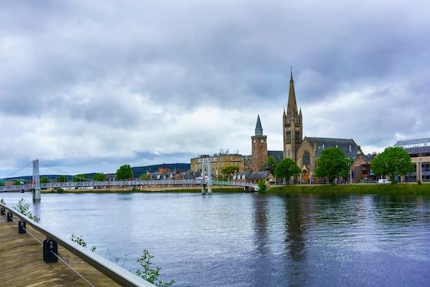 Schönes stadtbild von inverness, wo der fluss ness den moray firth mit blick auf die greig street bridge mit der free north church of scotland im hintergrund im sommer trifft, schottland
