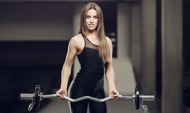 Schönes starkes athletisches muskulöses junges kaukasisches fitnessmädchen-trainingstraining im fitnessstudio