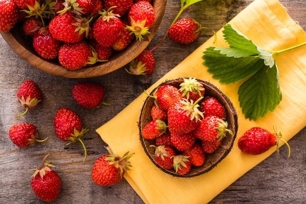 Schönes stillleben mit erdbeeren in hölzerne schüsseln. ansicht von oben