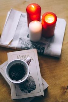 Schönes stillleben von büchern, kerzen und schwarzem kaffee auf dem tisch
