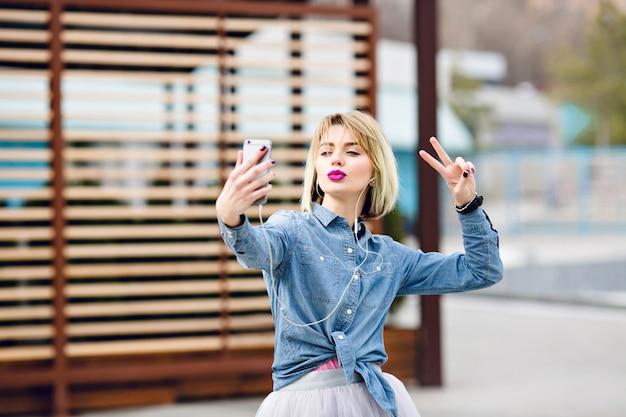 Schönes stilvolles blondes mädchen hat spaß und macht selfie mit einem kussgesicht und mit siegeszeichenfingern mit gestreiften braunen holzbalken dahinter