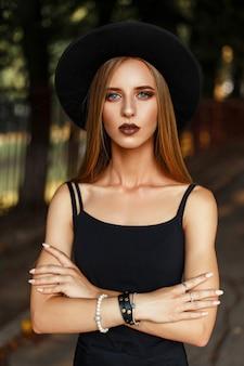 Schönes stilvolles frauenmodell im schwarzen modehut im park
