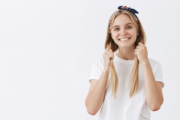 Schönes stilvolles junges blondes mädchen, das gegen die weiße wand aufwirft