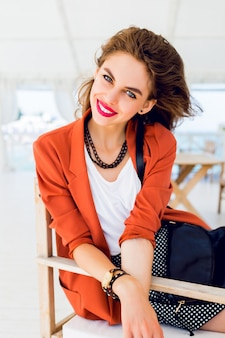 Schönes stilvolles junges freundschaftsmädchen, das im sommerrestaurant sitzt und träumt. fröhliche sonnige sommerferienstimmung, helle farben. habe volle rote lippen und große blaue augen.