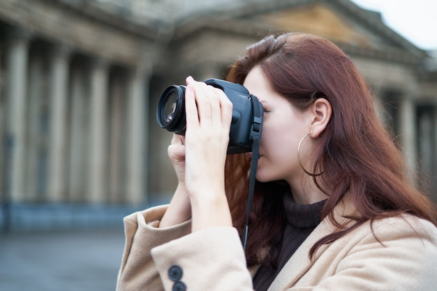 Schönes stilvolles modernes mädchen hält kamera in ihren händen und macht fotos.
