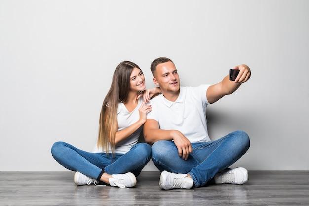Schönes stilvolles paar, das selfie zusammen lokalisiert auf weißem hintergrund macht