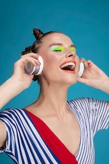 Schönes stilvolles weibliches modell mit hellem make-up, das musik hört und lächelt