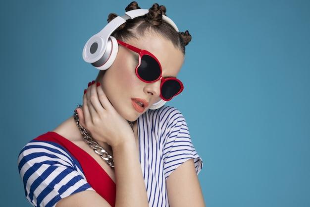 Schönes stilvolles weibliches modell mit sonnenbrille, die musik in den kopfhörern hört