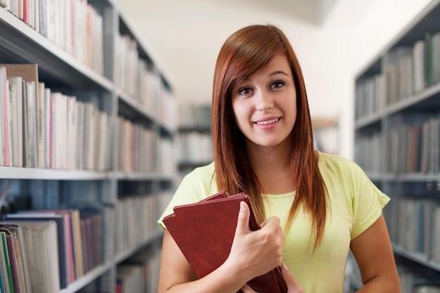 Schönes studentenmädchen, das bücher in der bibliothek hält
