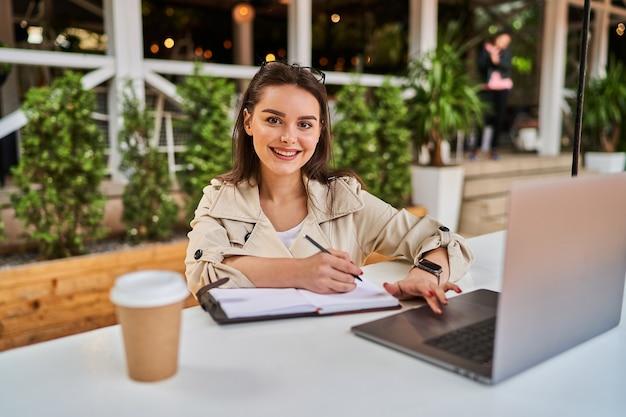 Schönes studentenmädchen, das online im freien mit kaffee zum mitnehmen lernt.